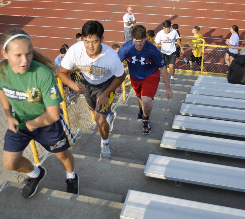 Students climb stairs in Physical Education class at Pius X High School